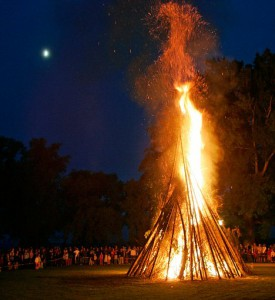 Midsummer bonfire against a night sky, moon