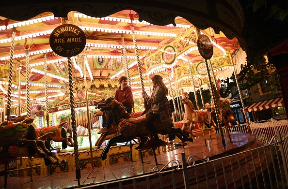 Members of the public ride a carousel adjacent to the 'St Nicholas Fair' Christmas market in the city centre of York, Northern England on December 3, 2014. AFP PHOTO / OLI SCARFF        (Photo credit should read OLI SCARFF/AFP/Getty Images)