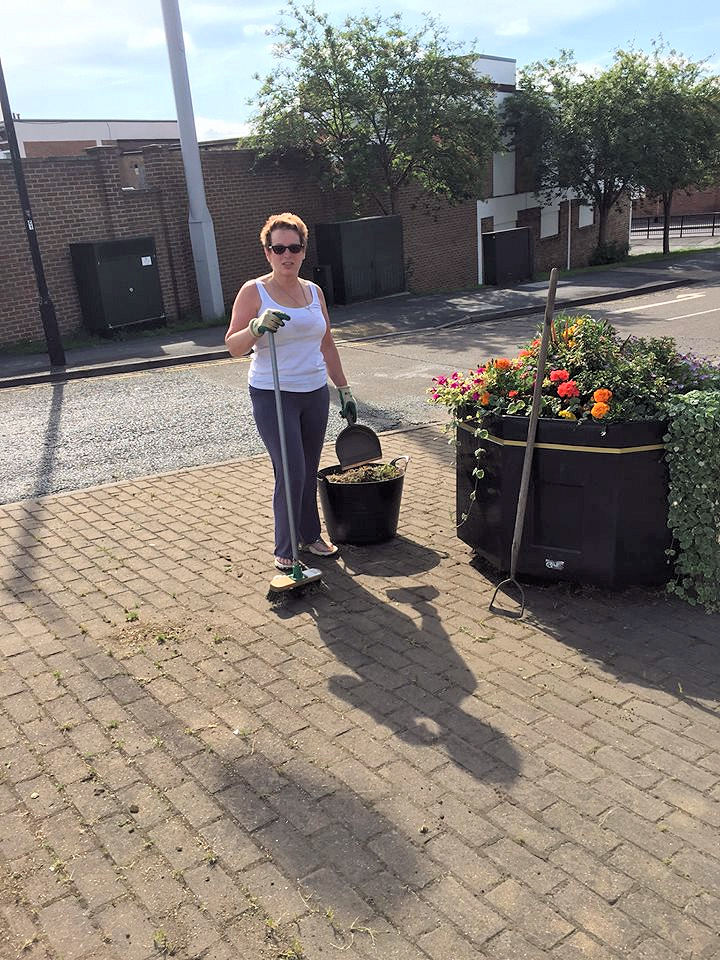 Cllr Sue Hunter helps to clean up paving on the Front Street link road